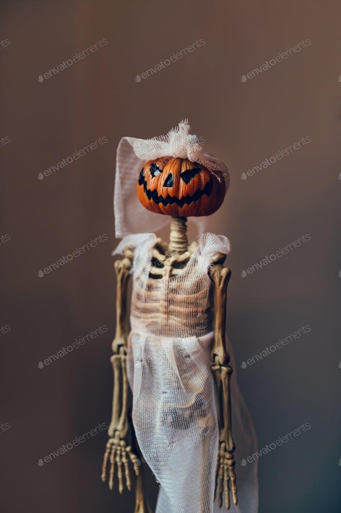 Skeleton with pumpkin head in bridal oufit