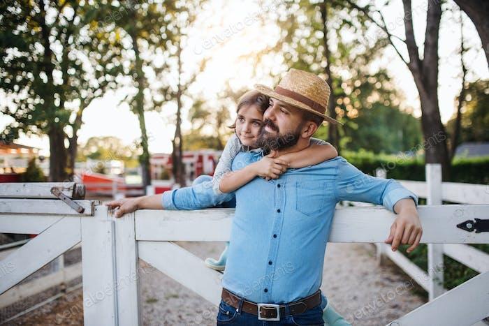 Ein Porträt von Vater mit kleiner Tochter im Freien auf Familienfarm