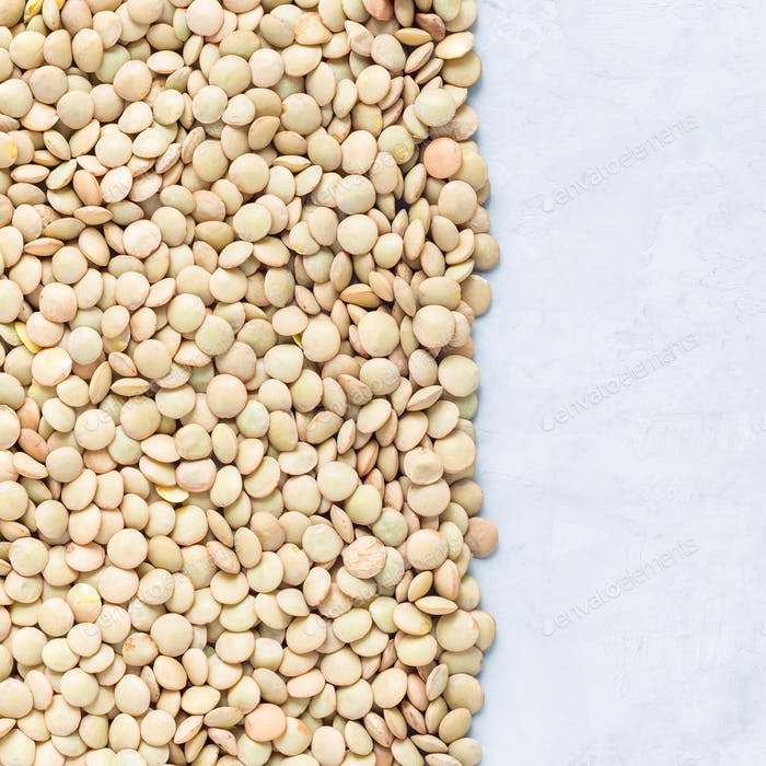 Uncooked dry green lentils on concrete background, top view, square