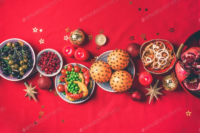 Vegan Christmas appetizers, olive, orange, fruits, vegetable salads, candles, tangerine, pomegranate