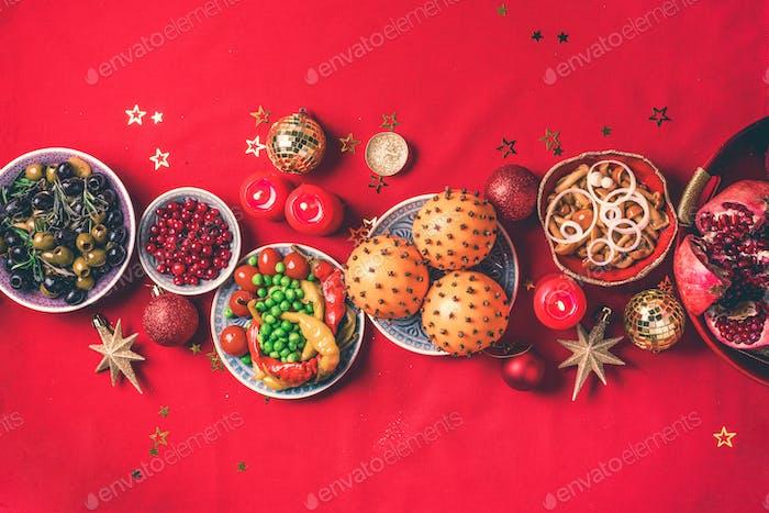 Aperitivos veganos de Navidad, oliva, naranja, frutas, ensaladas de verduras, velas, mandarina, granada