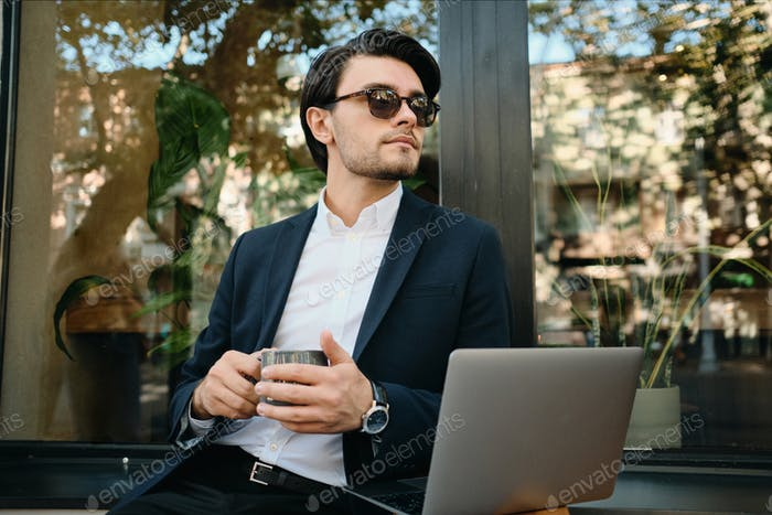 Stylish man in sunglasses working with laptop dreamily looking aside drinking coffee at cafe