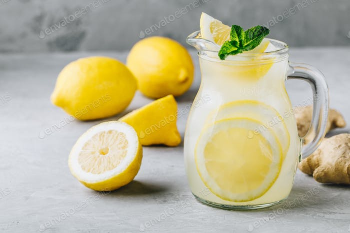 Homemade refreshing summer lemonade drink with lemon slices, ginger and ice
