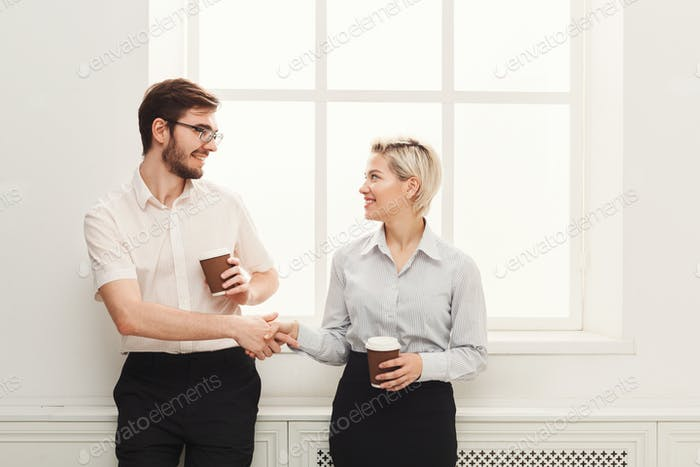 Couple of young colleagues drink coffee near window