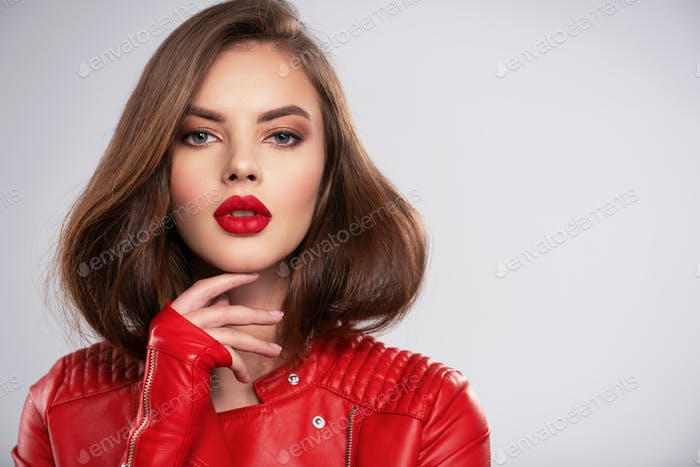 beautiful young woman with bright makeup. Beautiful brunette with bright red lipstick