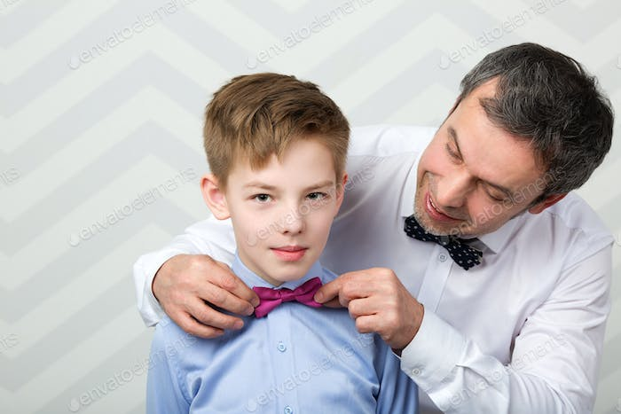 Father adjusting sons bowtie