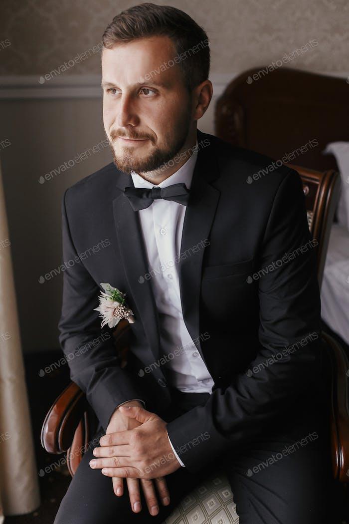 Стильный жених в черном костюме и галстук-бабочка, сидя в кресле на оконном свете