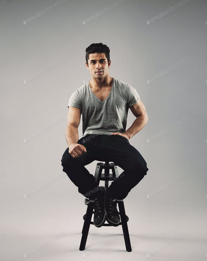 Smart young man sitting on stool