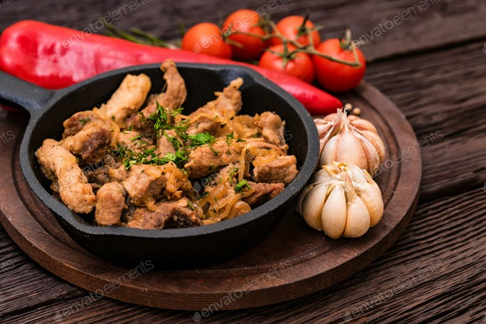 Fried pork in frying pan and vegetables