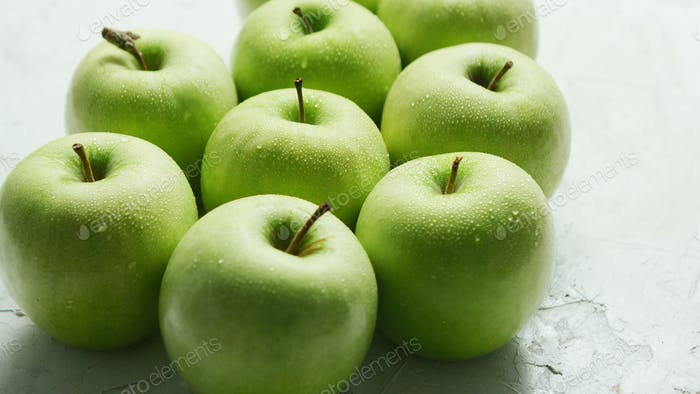 Ripe green apples in drops