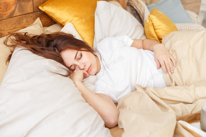 Portrait of a young girl sleeping on a pillow.