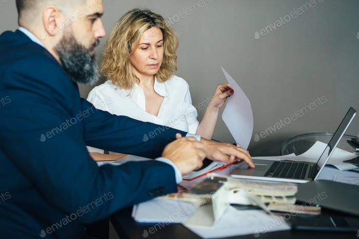 Two colleagues at table working on laptop