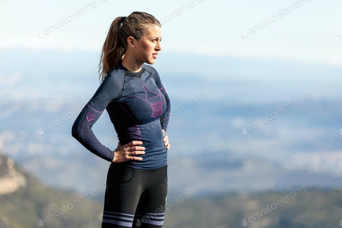 Trail runner standing and taking a break while looking landscape