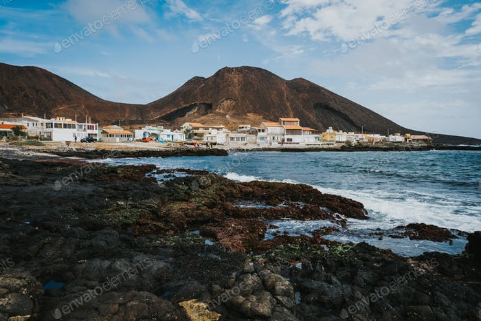 Calhau village on ocean coast in front of red colored volcanic crater. Cape Verde - Sao Vicente