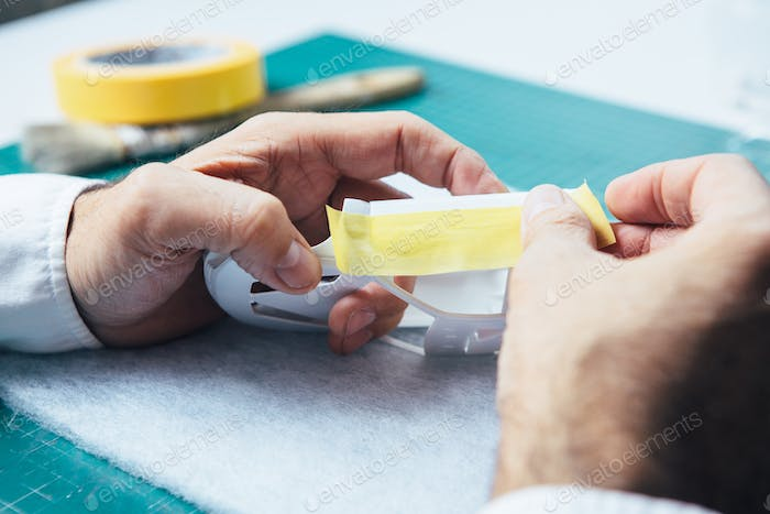 Person using tape for slot car painting