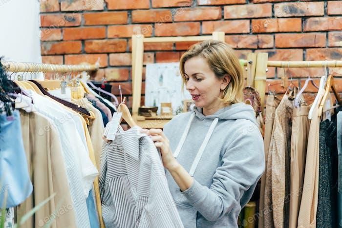 Candid Woman Shopaholic wählt modische Kleidung im Showroom.