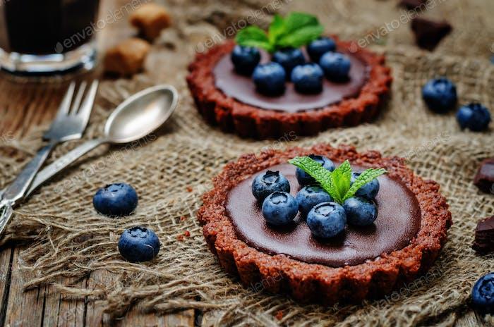 Schokoladentörtchen mit Schokoladenfüllung und frischen Heidelbeeren