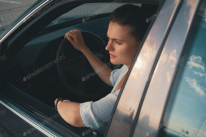 Young woman in casual wear Put Head Out of Window  while driving