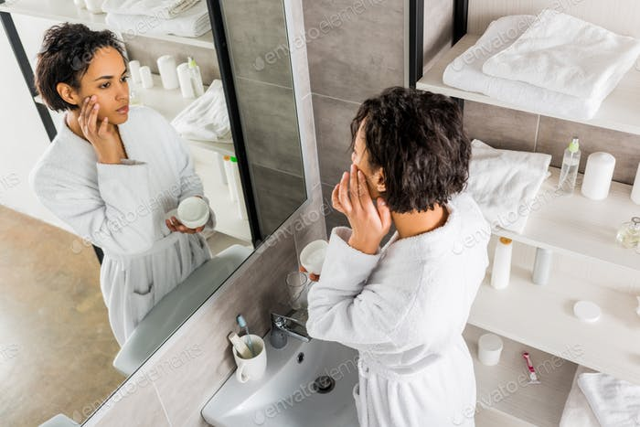 afroamerikanische Frau, die kosmetische Anti-Falten-Creme auf das Gesicht aufträgt und in den Spiegel schaut