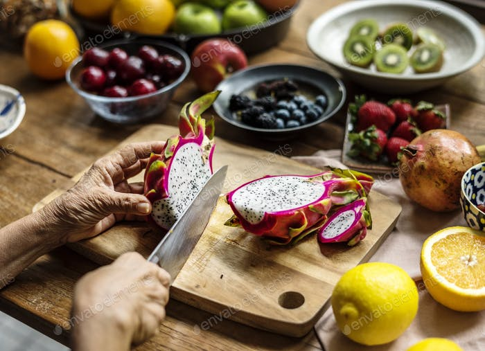 Closeup of hand with knife cutting dragon fruit