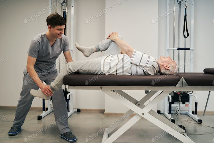 Pensioner stretching right leg while doctor pulling his left one
