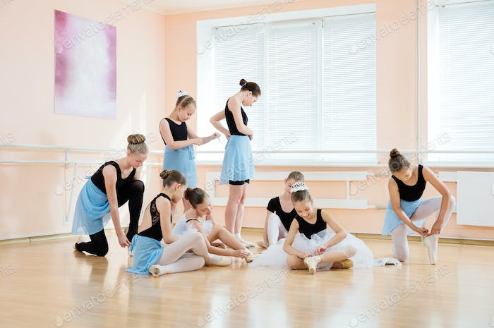 Young ballerinas putting on pointe shoes and adjusting costumes