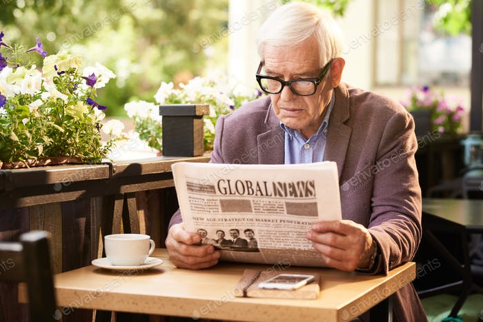 Senior Man Reading Newspaper in Outdoor Cafe