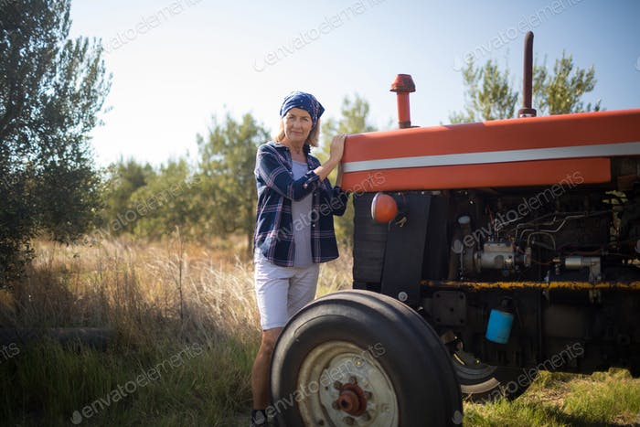Portrait of confident woman standing near tractor in olive farm