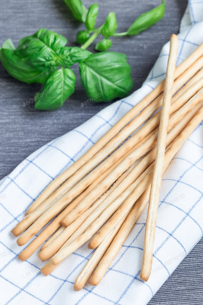 Traditional Italian snack grissini bread sticks with basil leave