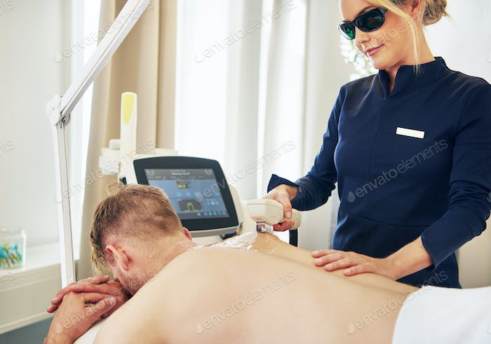 Young beauty technician performing laser hair removal on a client