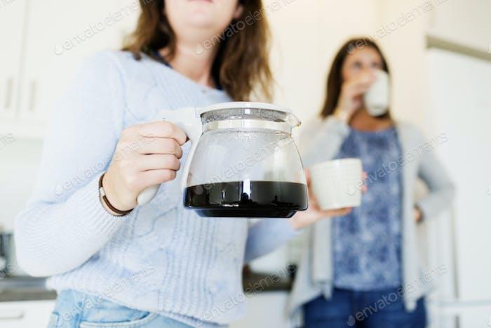 Mittelteil der Frau hält Wasserkocher, während Freund Kaffee trinken in neuen Hause