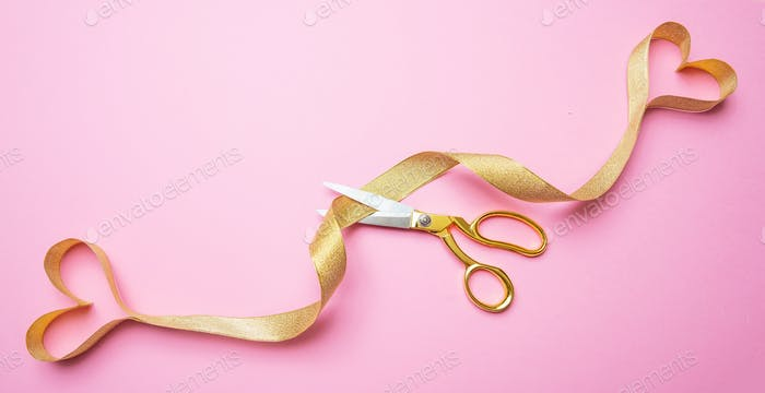 Gold scissors cutting golden ribbon ending in two hearts, pink background, top view.