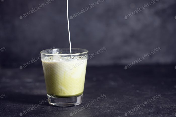 Green matcha latte with pouring milk on a black background with copy spase