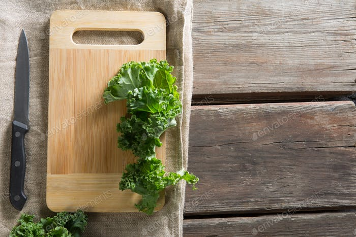 Kale leaves on cutting board with knife at table