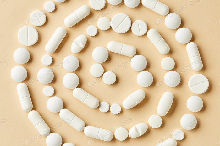 white medicine pills on beige background