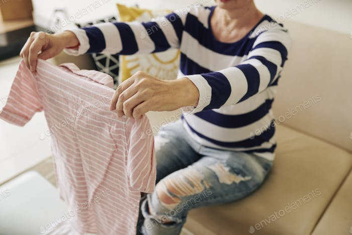 Woman holding creased striped shirt