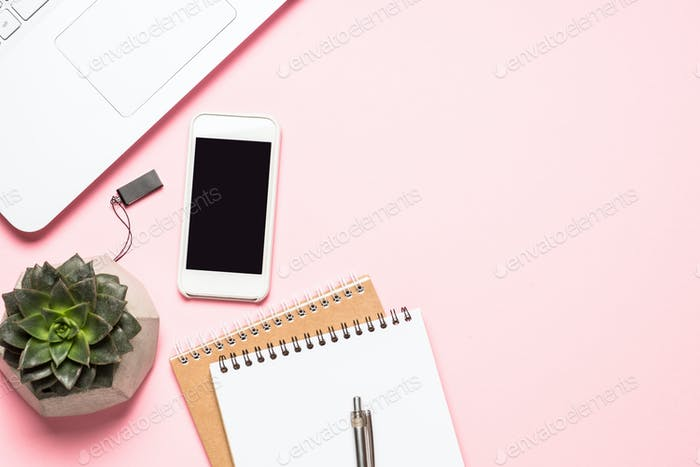 Office workplace with notepad, smartphone and cactus on pink background.