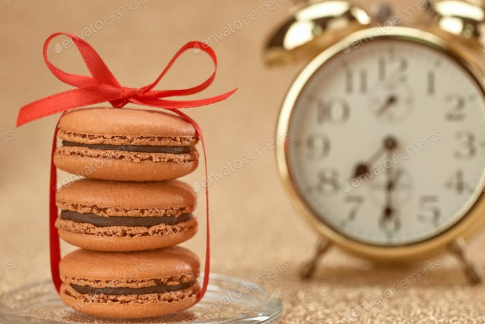 Macarons. Gold stylish alarm clock, breakfast time