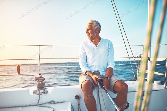 Mature man sailing his boat on the open ocean