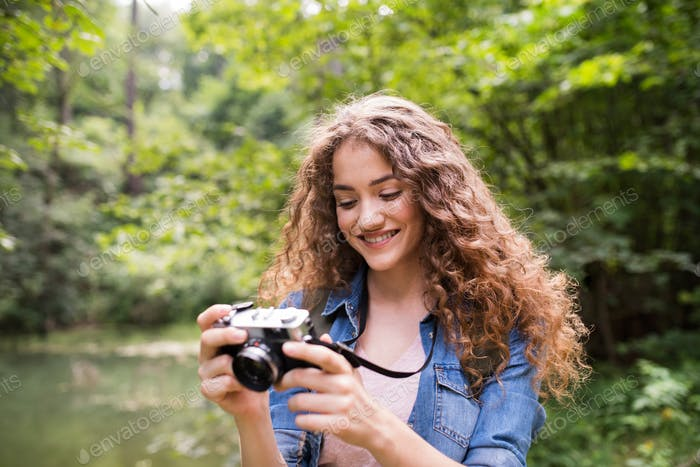 Teenage girl hiking in forest, taking pictures with camera.