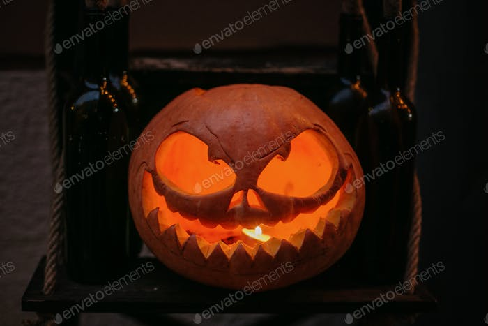 Pumpkin with scary carved glowing face and candle light in dark, modern festive decoration