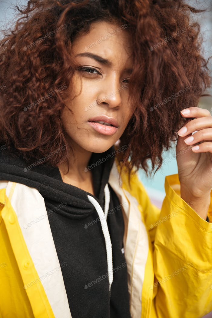 Serious african curly young woman wearing yellow coat