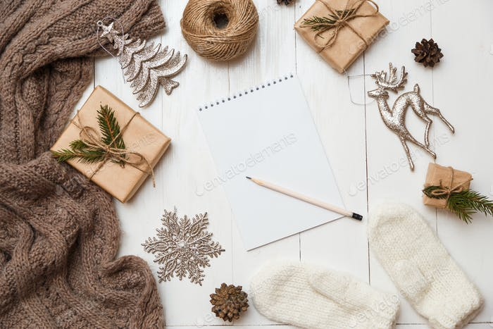 Gifts, and notepad on wooden table. Christmas or new year concept. Flat lay, top view