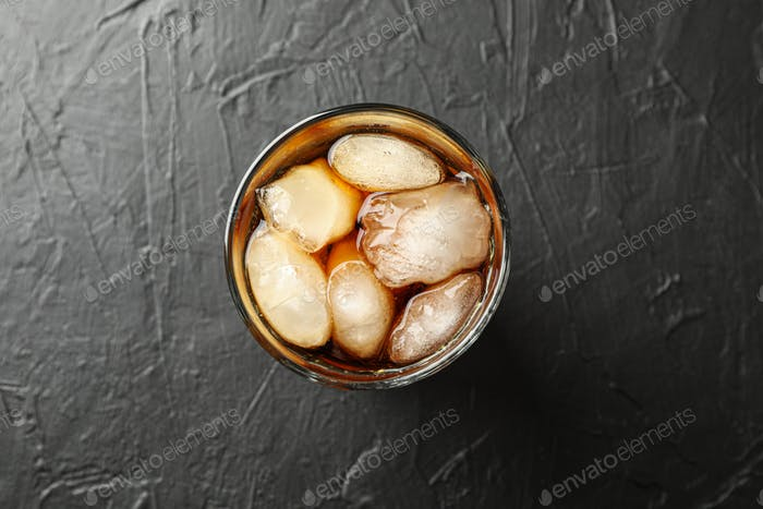 Glass of cold cola on black cement background
