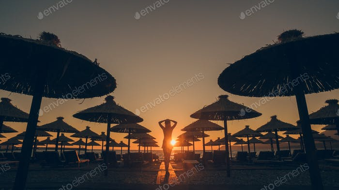 girl look at sunset on beach silhouette