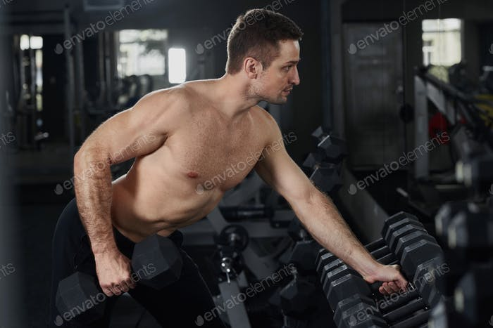 Hot muscular man with naked torso and holding dumbbell weight
