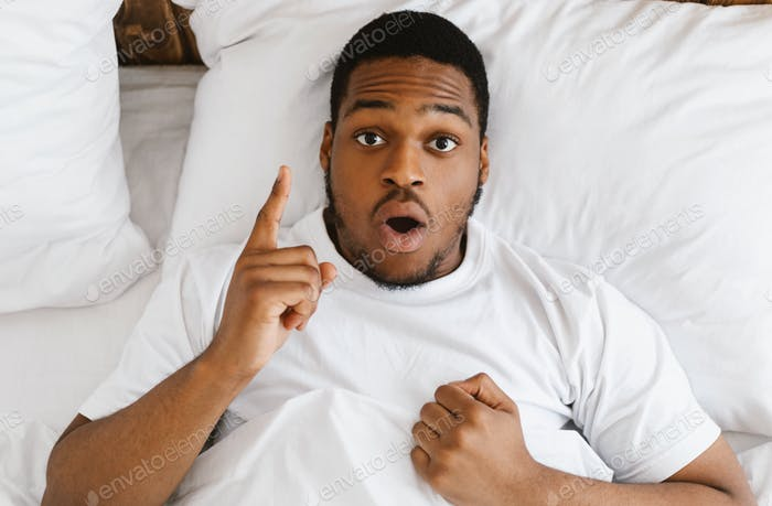 African American Man Having Idea Lying In Bed At Home