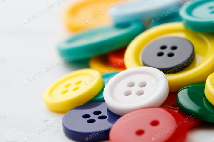 Close up of pile of colorful buttons on white background