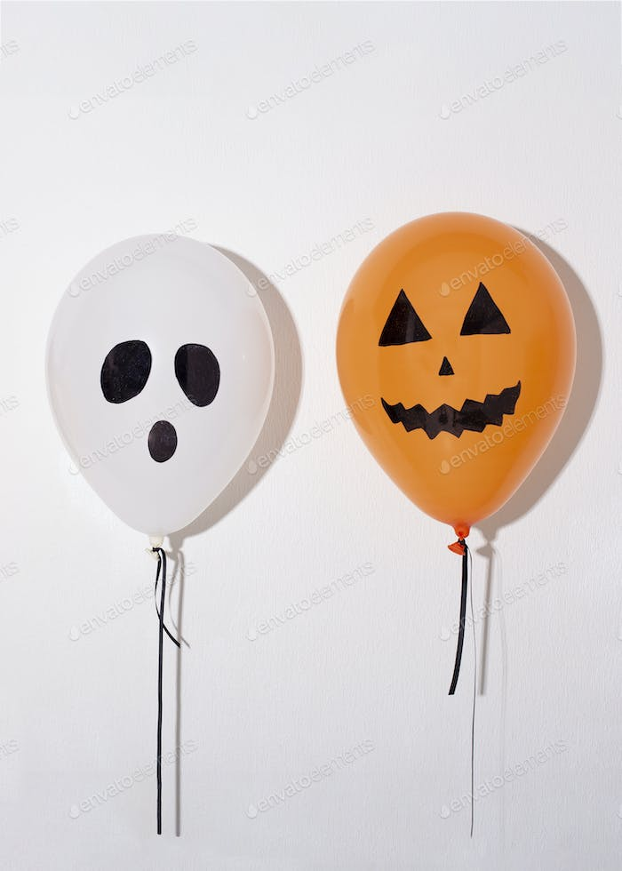 Halloween balloons with funny faces on white background