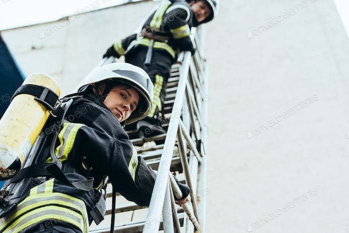 low angle view of firefighters in helmets standing on ladder and looking at camera